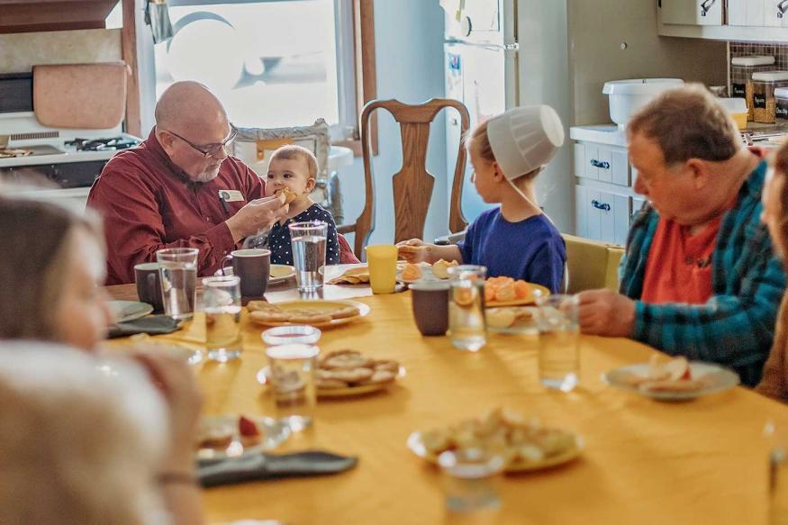 Group of tourists sharing a meal with an Amish family