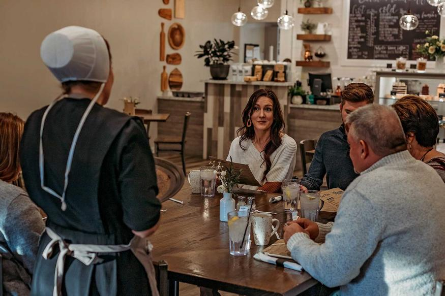 Family at a restaurant being served by an Amish woman