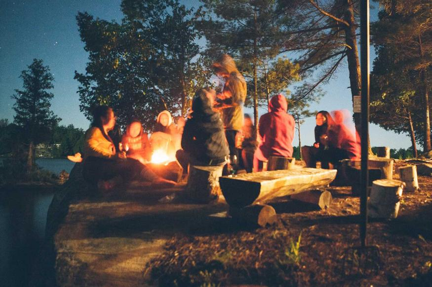 Group of friends around a campfire at night